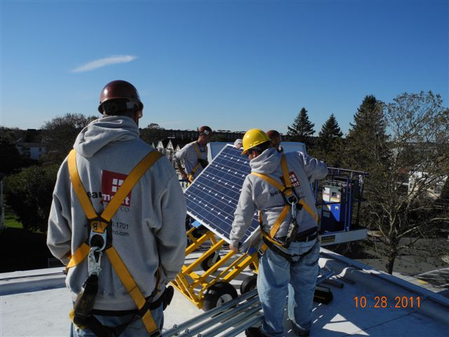 Beaumont Solar's in-house installation crew offloads the solar panels onto the roof