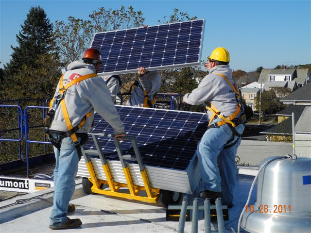 Panels being brought to roof for system layout