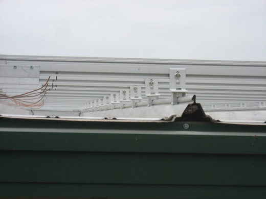 Underside view of solar racking system installed on standing seam metal roof
