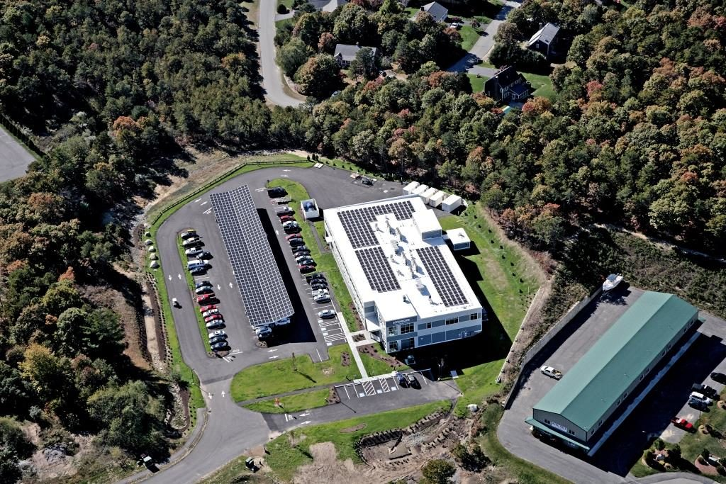 Aerial view of the entire carport and rooftop solar system engineered, designed and constructed by Beaumont Solar at Hydroid Inc in Pocasset, MA.