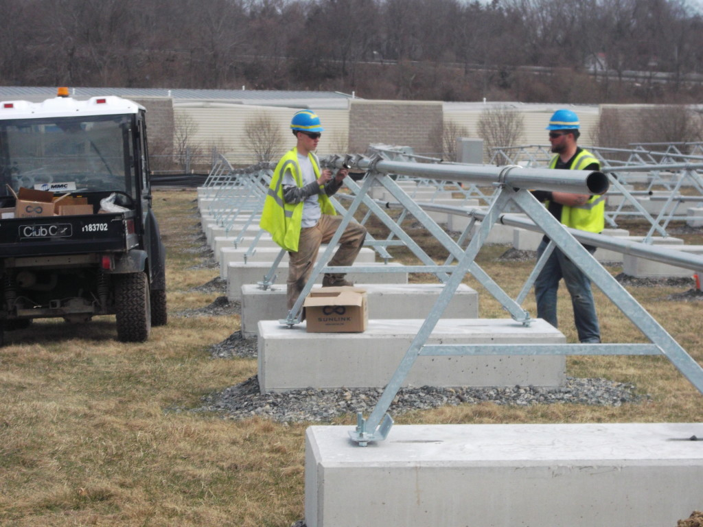 A member of the Beaumont Solar apprentice team installs the clips to the rails that will receive the solar panels