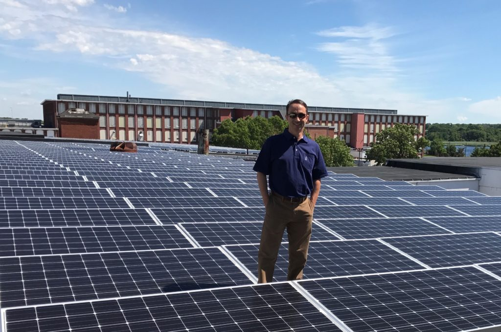 Jeff Glassman, President of Darn It! Inc. in New Bedford, MA stands amongst a section of his 516kW rooftop solar system on a beautiful New England day.  Glassman first had Beaumont Solar install a 281.6kW system back in 2011.  Seeing the benefits of the solar, Mr. Glassman contacted Beaumont Solar again to install an additional 234.5kW solar system.