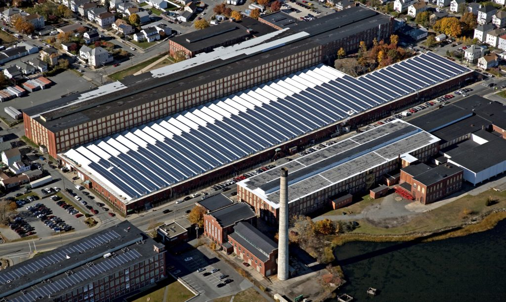 This circa 1909 mill building, which houses the Joseph Abboud Manufacturing Corporation in New Bedford, with a saw-tooth roof now produces 70% of its own clean electricity