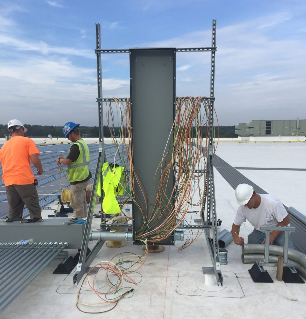 Beaumont Solar electricians preparing for main panelboard.  Inverter runs into the junction box can be seen on the bottom left.