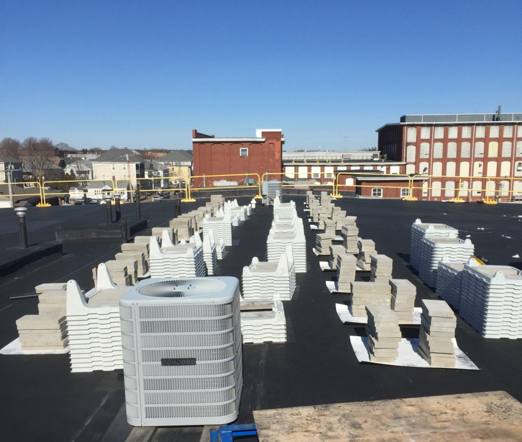The Beaumont Solar engineering team designed this system to use a non-penetrating, ballasted solar racking system, as seen here prior to being laid out.