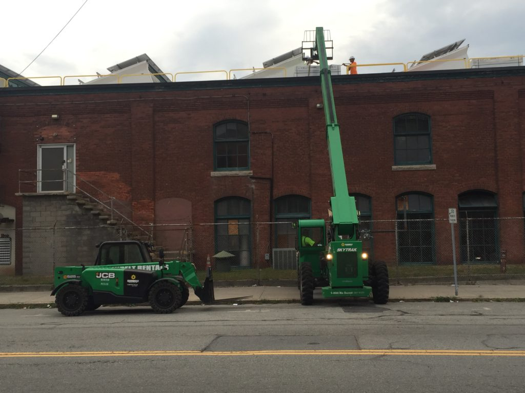 Crews hoist the panels to the roof to get ready for construction now that the safety rails have been installed.
