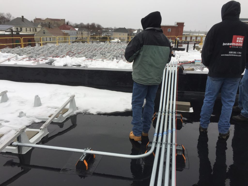 View of the piping work by Beaumont Solar's electrical team that brings the DC wiring from the roof to the tie in points.